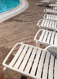 Loungers and pool. Lounge chairs along the edge of the pool royalty free stock photos