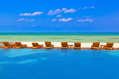 Loungers and pool on Maldives beach. Nature vacation background stock images