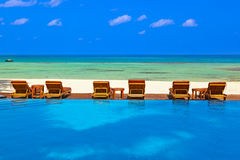 Loungers and pool on Maldives beach Stock Photography