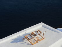 Loungers in Santorini. Two chairs on the roof of one of Oia's signature white buildings have an overwhelming view of the caldera and Aegean Sea Stock Photos