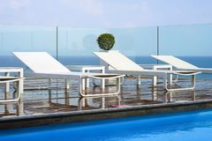 White summer sun loungers on a wooden floor royalty free stock photography