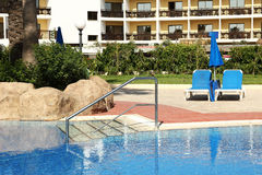 Loungers by the swimming pool water. A loungers by the swimming pool water stock image