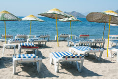 Loungers and umbrellas on beach. Sun loungers and wicker parasols on sandy beach in Turgutreis in the Bodrum Peninsula, Turkey Royalty Free Stock Photo