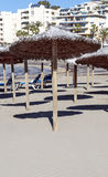 Loungers and umbrellas. On the beach of Estepona on the Costa del Sol in Malaga on a summer day with hotel in the background Stock Photography