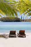 Loungers under a palm tree on a tropical beach. Isle od Pines, New Caledonia Royalty Free Stock Image