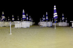 Lounges and closed umbrellas on night beach Royalty Free Stock Photos