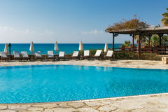 Lounges near the pool. Lounges standing near the empty pool in luxury mediterranean hotel Royalty Free Stock Photo