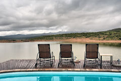 Lounges between swimming pool and lake in mountains. Shot in a game lodge near Oudtshoorn, Western Cape, South Africa Royalty Free Stock Photos