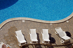 Lounges by swimming pool Royalty Free Stock Image