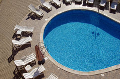 Lounges by swimming pool Stock Images