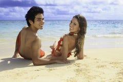 lounging在夏威夷海滩的夫妇 库存照片