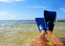 Lounging. On beach, in shallow water, with snorkel fins on Stock Image