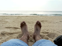 Lounging on the beach 3. Photo of a pair of feet lounging in the sand at VA Beach royalty free stock image