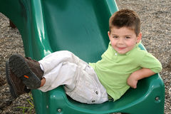 Lounging Boy With A Secret. Young boy lounging across the bottom of a sliding board, with his feet crossed stock photo