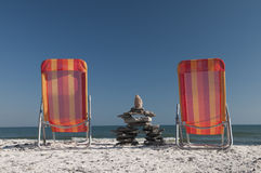 Lounging With Inukshuk. Inudshuk sitting between two lounging chairs resting on the Lake Ontario shoreline Royalty Free Stock Photography