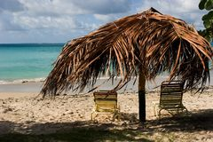 Lounging in the tropics. Two beach chairs and palm shade on tropical beach stock image