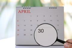 Loupe à disposition sur le calendrier que vous pouvez sembler de trente jours de Photo libre de droits