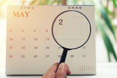 Loupe à disposition sur le calendrier vous pouvez regarder le deuxième jour de Photographie stock libre de droits