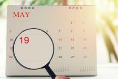 Loupe à disposition sur le calendrier vous pouvez regarder le dix-neuvième jour Photographie stock libre de droits