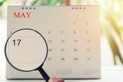 Loupe à disposition sur le calendrier vous pouvez regarder le dix-septième DA Image stock