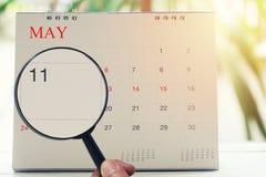 Loupe à disposition sur le calendrier vous pouvez regarder le jour onze de Images stock