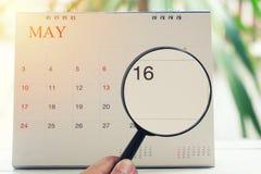 Loupe à disposition sur le calendrier vous pouvez regarder le jour seize de Photos stock