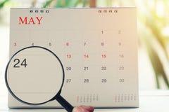 Loupe à disposition sur le calendrier vous pouvez regarder les vingt-quatre DA Photographie stock