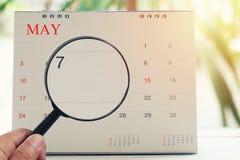 Loupe à disposition sur le calendrier vous pouvez regarder le septième jour de Image stock