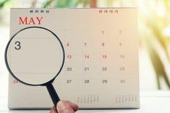 Loupe à disposition sur le calendrier vous pouvez regarder le troisième jour de m Images stock