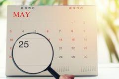 Loupe à disposition sur le calendrier vous pouvez regarder vingt-cinq DA Photos libres de droits