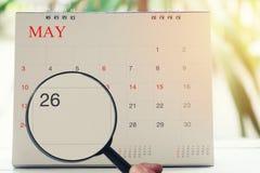 Loupe à disposition sur le calendrier vous pouvez regarder vingt-six jours Photo stock