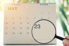Loupe à disposition sur le calendrier vous pouvez regarder vingt-trois d Photographie stock libre de droits