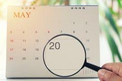Loupe à disposition sur le calendrier vous pouvez regarder le vingtième jour Photo stock