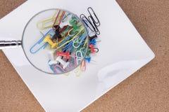 Loupe au-dessus des trombones et des goupilles de dessin colorés Photographie stock