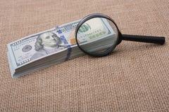 Loupe au-dessus du paquet de billet de banque du dollar US Photos libres de droits