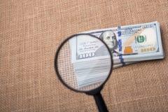 Loupe au-dessus du paquet de billet de banque du dollar US Photographie stock
