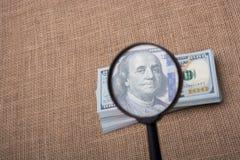 Loupe au-dessus du paquet de billet de banque du dollar US Images libres de droits