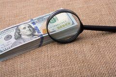 Loupe au-dessus du paquet de billet de banque du dollar US Photo libre de droits