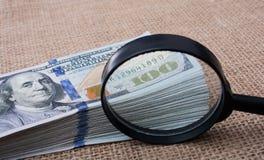 Loupe au-dessus du paquet de billet de banque du dollar US Image stock