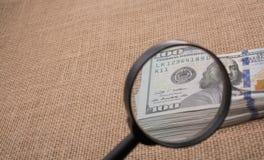 Loupe au-dessus du paquet de billet de banque du dollar US Image libre de droits