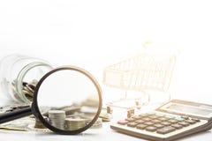 Loupe avec des piles des pièces de monnaie et du billet de banque du dollar sur le dos de blanc Photo stock