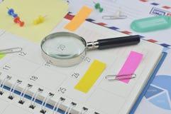 Loupe avec les notes de post-it colorées et goupille sur la PA de journal intime Image stock