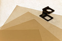 Loupe checking Formation of paper sheets Royalty Free Stock Images
