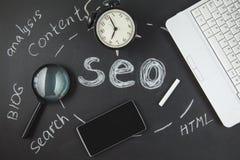 Loupe de concept d'optimisation de moteur de SEO Search, horloge, smartphone sur un fond noir avec une inscription SEO image libre de droits