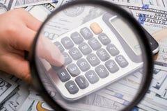 Loupe et calculatrice au-dessus des billets de banque de dollar US Image stock