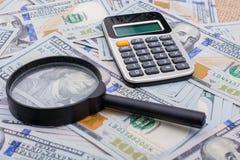 Loupe et calculatrice au-dessus des billets de banque de dollar US Images libres de droits
