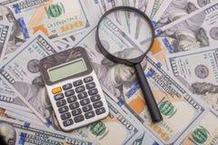 Loupe et calculatrice au-dessus des billets de banque de dollar US Photo libre de droits