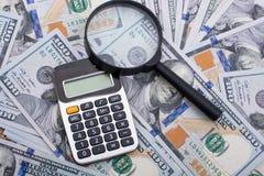 Loupe et calculatrice au-dessus des billets de banque de dollar US Photos stock