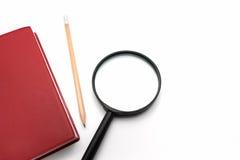 Loupe et carnet rouge de couverture sur le fond blanc Image stock
