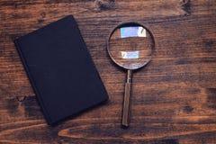Loupe powiększać - szkło i notatnik na drewnianym biurku, odgórny widok Zdjęcia Stock